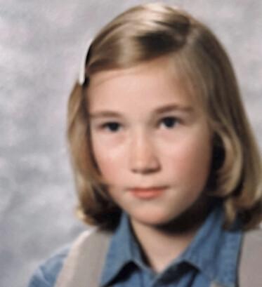 Christina har välkammat axellångt hår, sidbena och en vit klämma håller håret borta från ansiktet, blå skjorta och beige väst och ser allvarlig ut.
