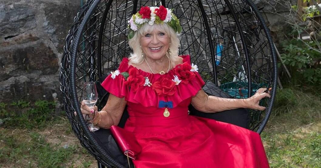 Christina Schollin i röd klänning och blomsterkrans.