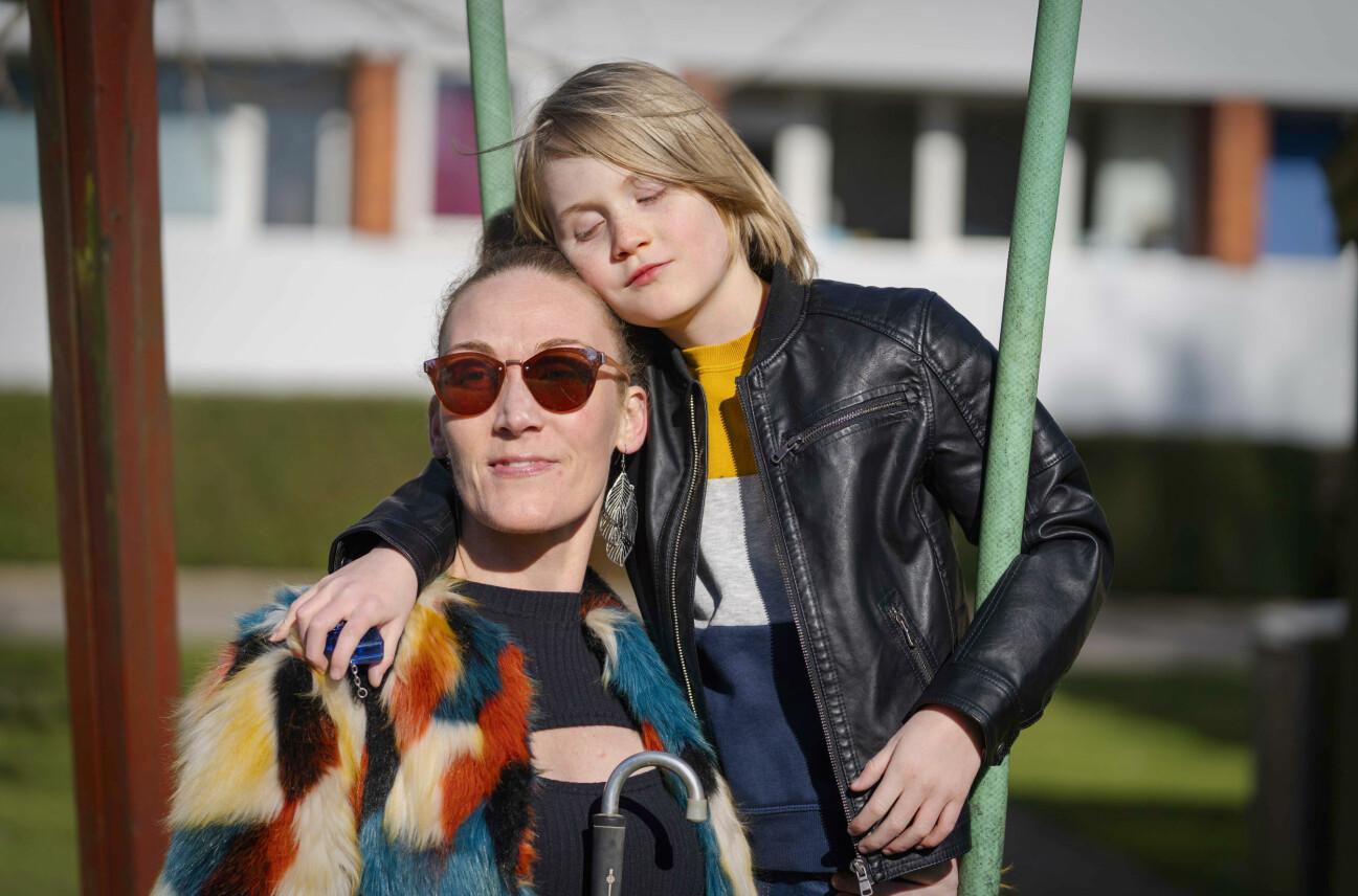 Christina sitter utomhus och bredvid henne står sonen Silas som håller om henne och lutar sitt huvud mot hennes.