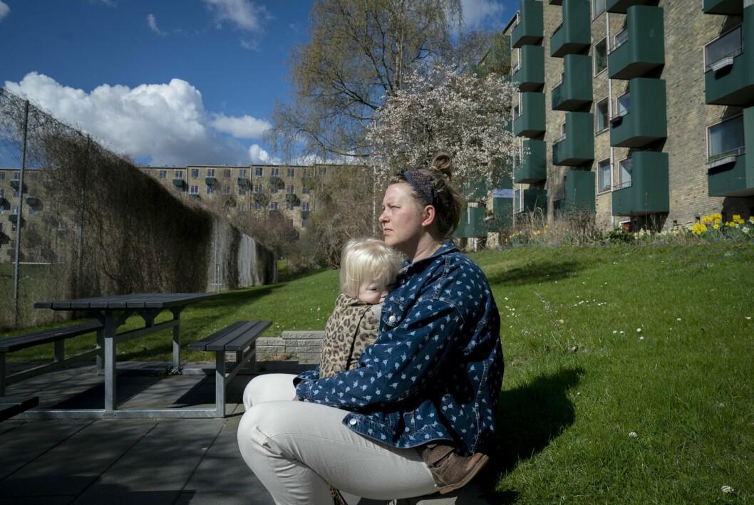 Christina ser allvarlig ut där hon sitter med sin tvååriga dotter i knät, mellan hyreshusen där de bor i Köpenhamn.