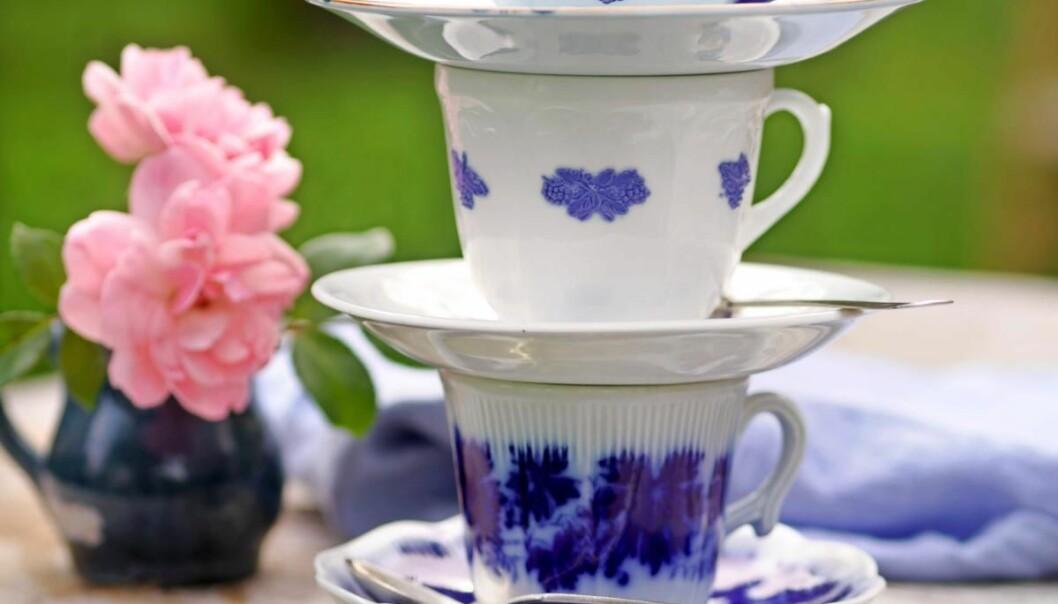 Tre blåvita kaffekoppar står staplade på varandra på ett träbord, bredvid två rosa blommor i en liten mörkblå vas.