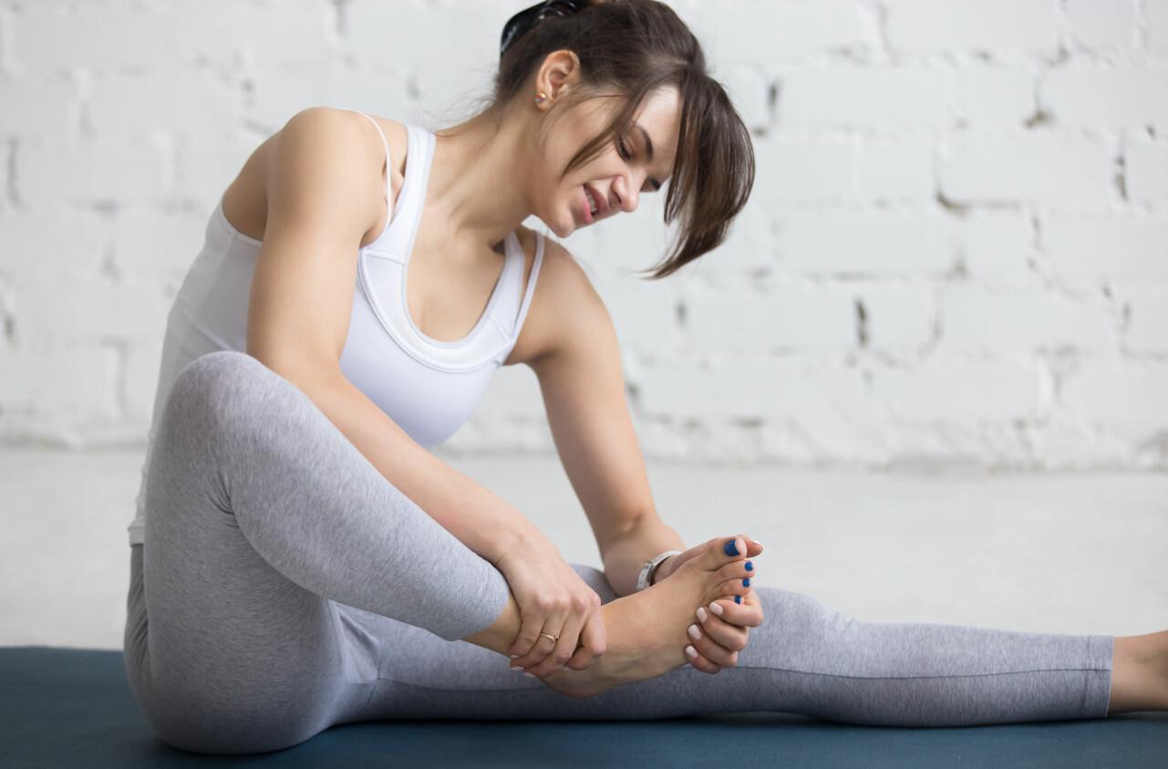 Kvinna med kramp under foten försöker stretcha bort problemet.