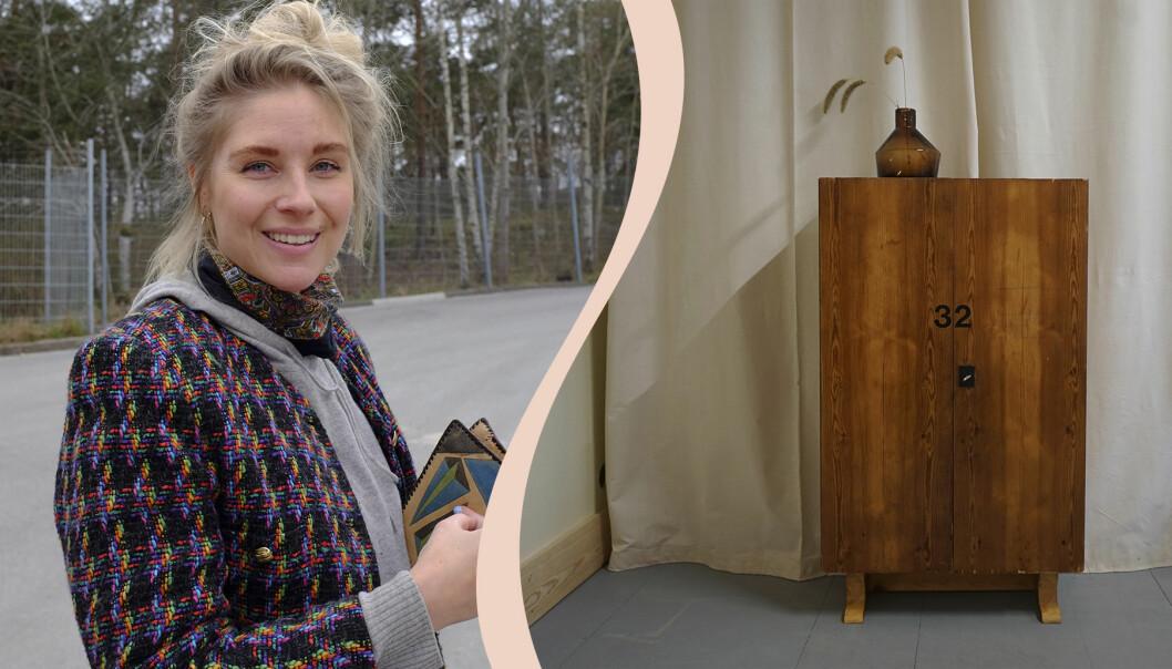 Frida Thofelt ler med staket och björkar utan löv i bakgrunden, till höger ett brunt skåp, ovanpå står en brun glasvas med tre axstråni.
