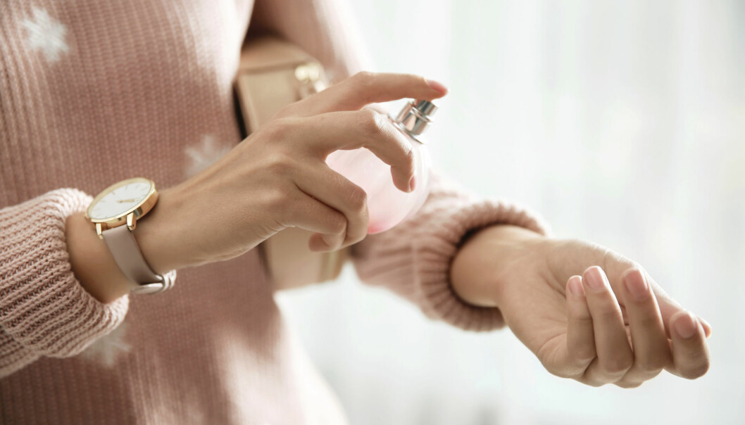 Young woman using perfume on her left wrist.