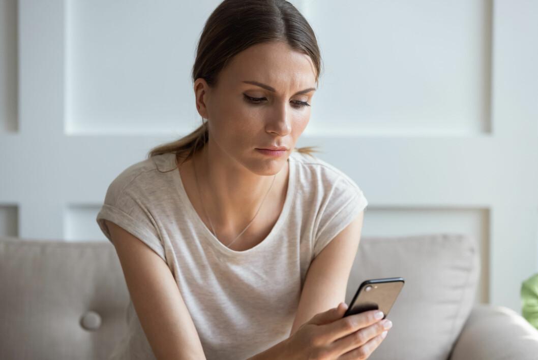 En kvinna sitter med sin mobiltelefon och scrollar.