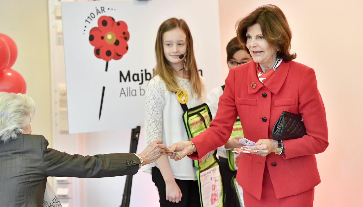 Drottningen Silvia är Majblommans höga beskyddare och köpte 2017 års första majblomma av elever på Maltesholmsskolan i Hässelby utanför Stockholm på torsdagen. Fjärdeklassaren Miranda Nilsson, Luleå, som har designat årets majblomma, och Zacharias Arrach, elev i årskurs 5 på Maltesholmsskolan, säljer årets majblomma till drottningen. När det var dags att betala fick dock hovdamen Christina von Schwerin hjälpa till. Drottning Silvia hade nämligen inte tillräckligt med kontanter