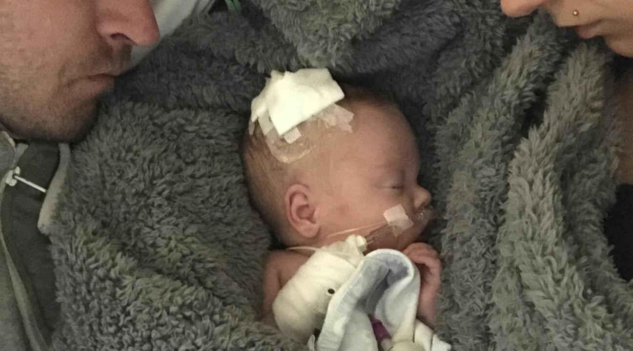 Elton ligger nyfödd på sjukhuset på en filt mellan mamma och pappa.