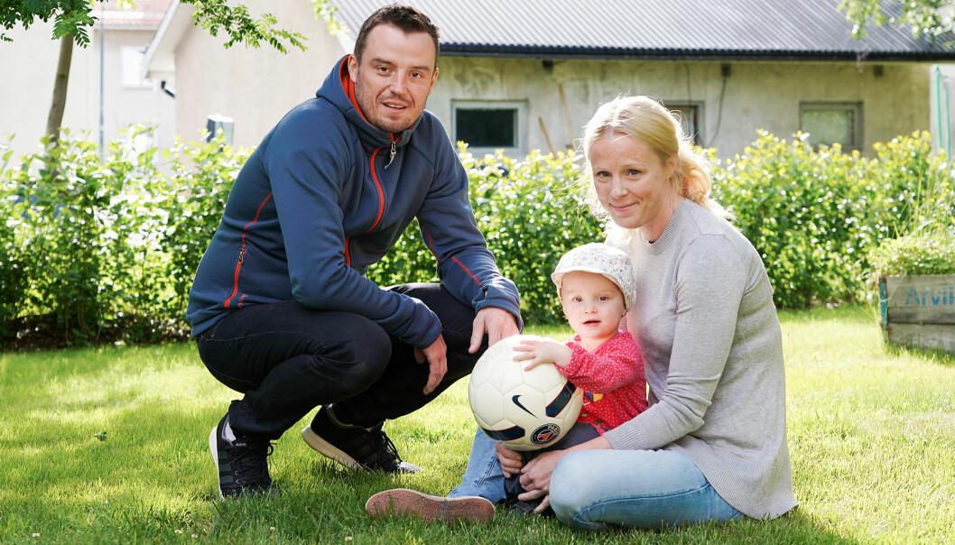 Ebba tillsammans med sina föräldrar på en gräsmatta
