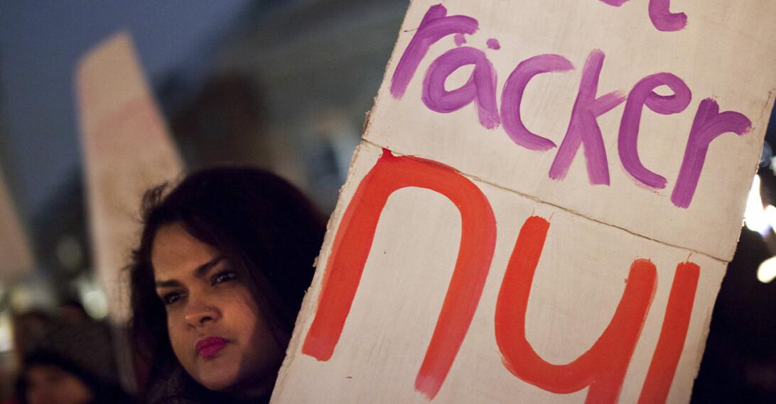 En kvinna håller upp en skylt med texten: Det räcker nu för att protestera mot mäns våld mot kvinnor