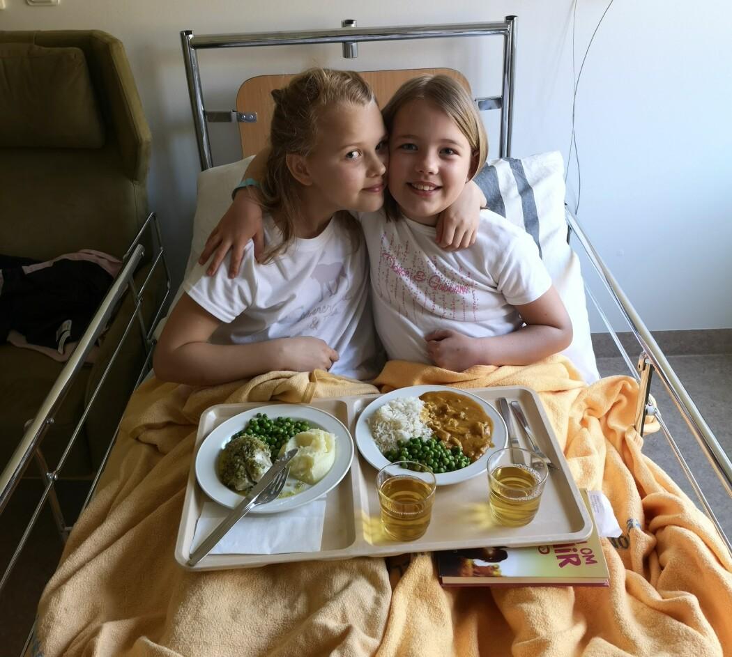 Elsa och Ellen är på sjukhuset för provtagning och sitter tillsammans i en sjukhussäng och har brickor med mat i knät