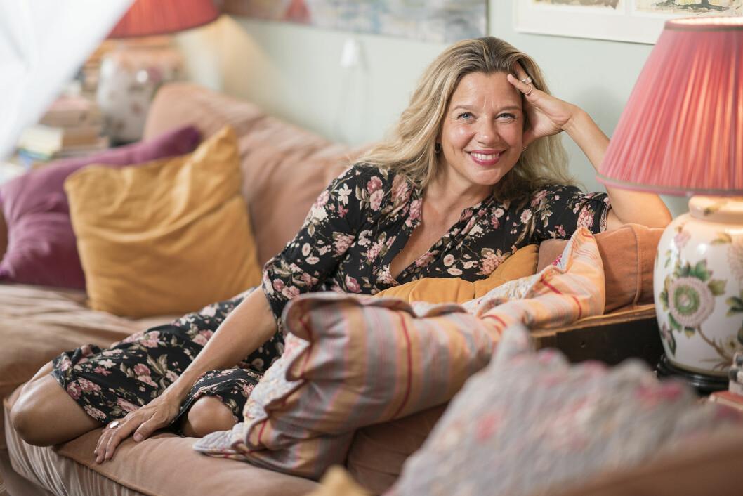 Emma Hamberg sitter i en soffa och ler mot kameran