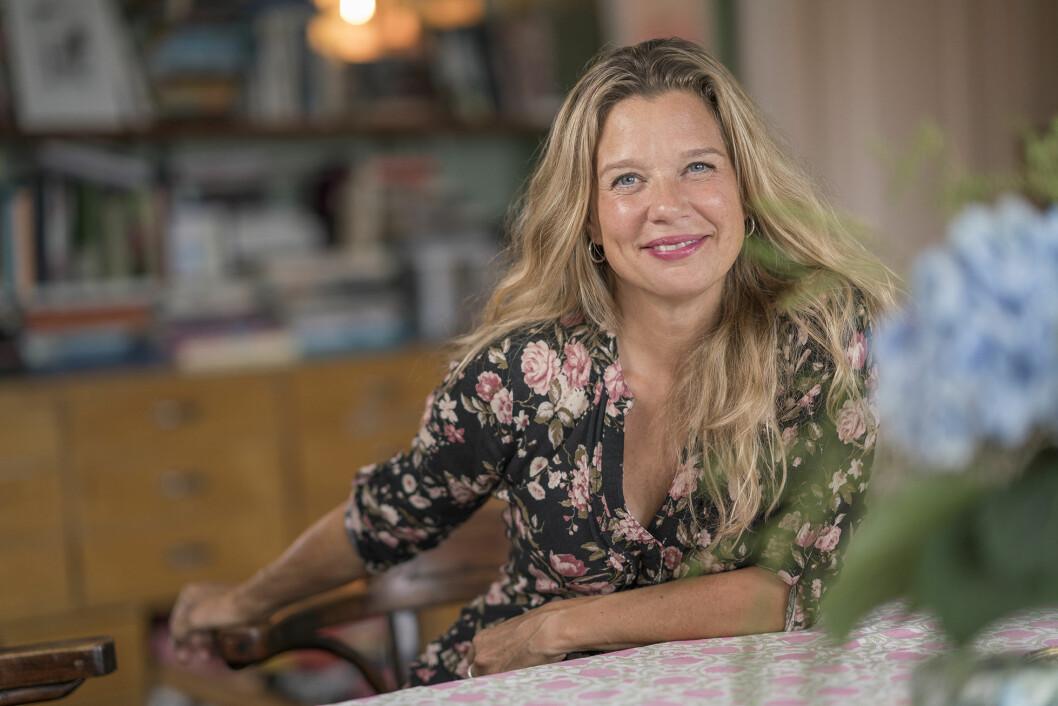 Författaren Emma Hamberg sitter vid ett bord och ler stort mot kameran.