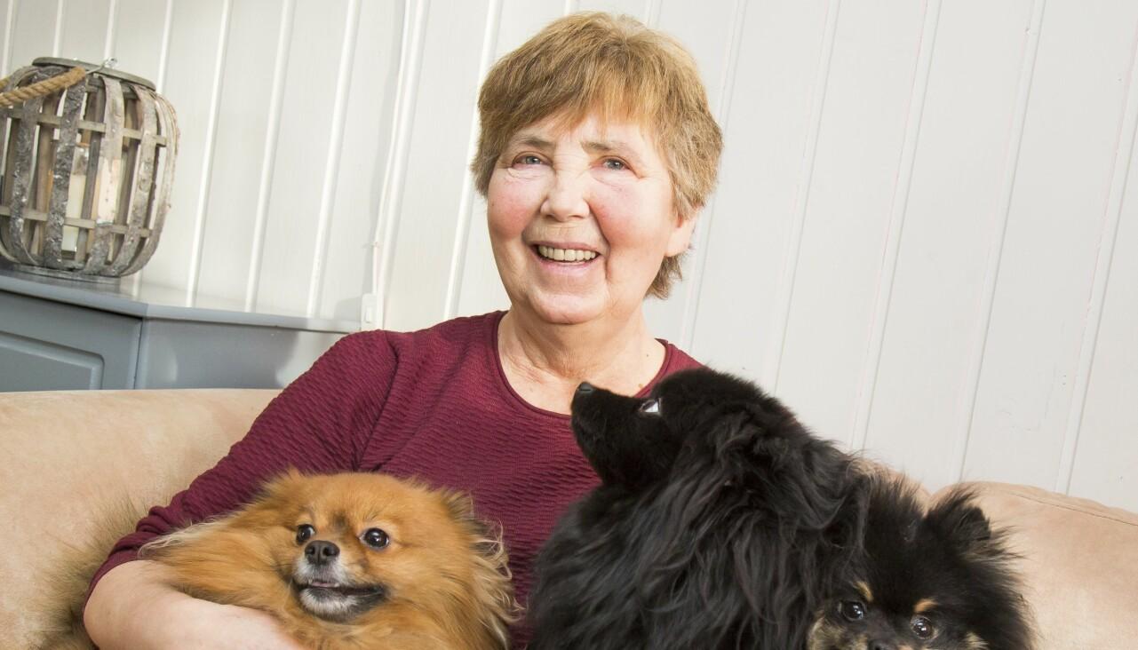 En äldre leende kvinna sitter i en soffa med sina tre hundar i knät.