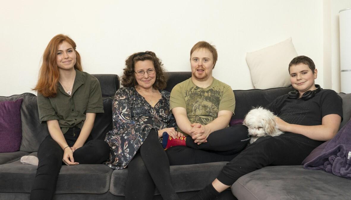 En familj sitter i soffan med en hund.