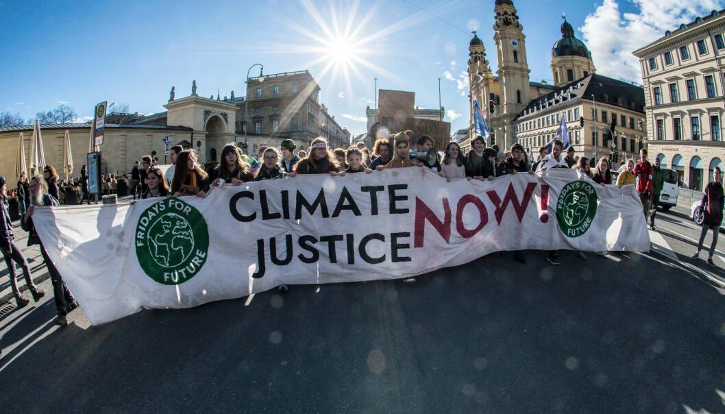 En grupp ungdomar strejkar för klimatet med en stor banderoll.