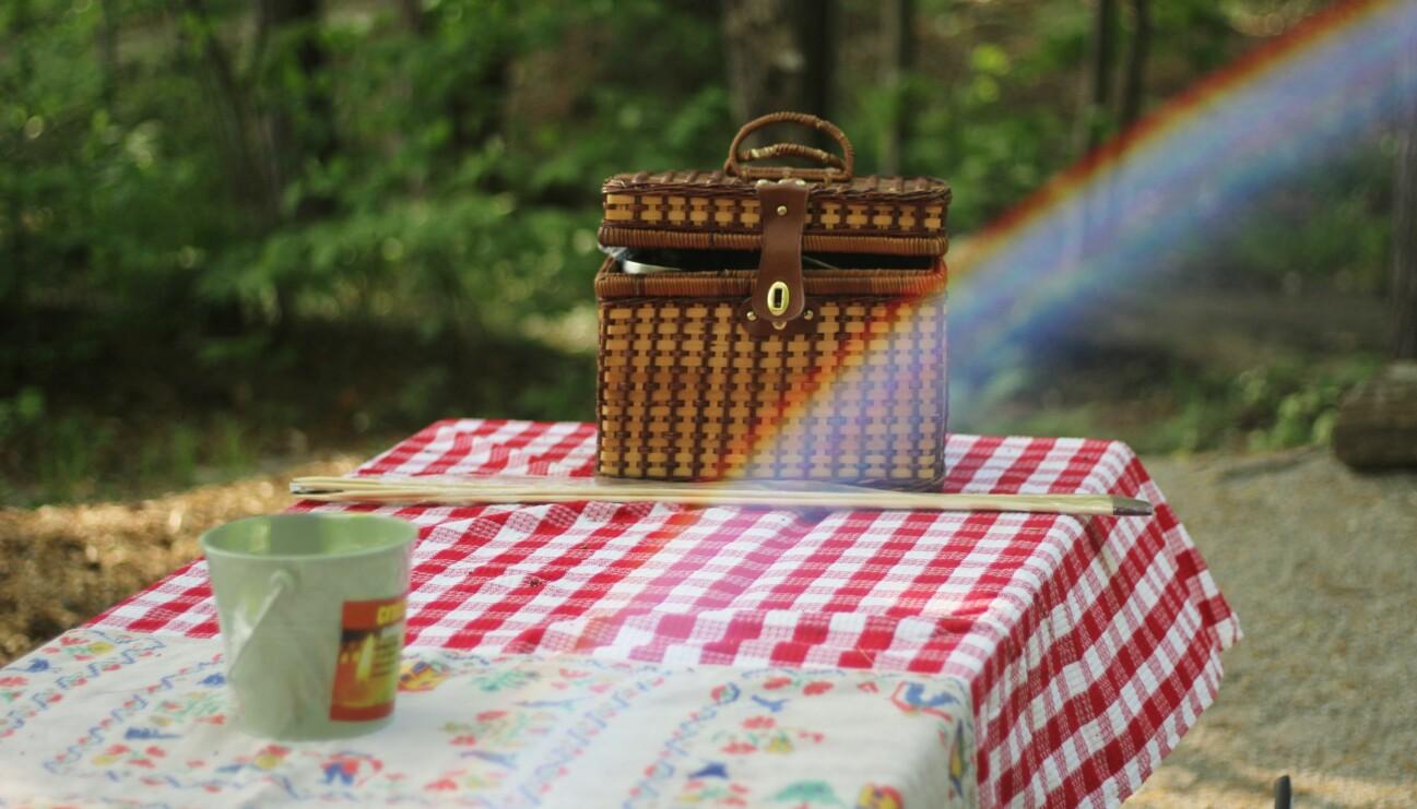 En korg och en kaffekopp på picnicbordet.