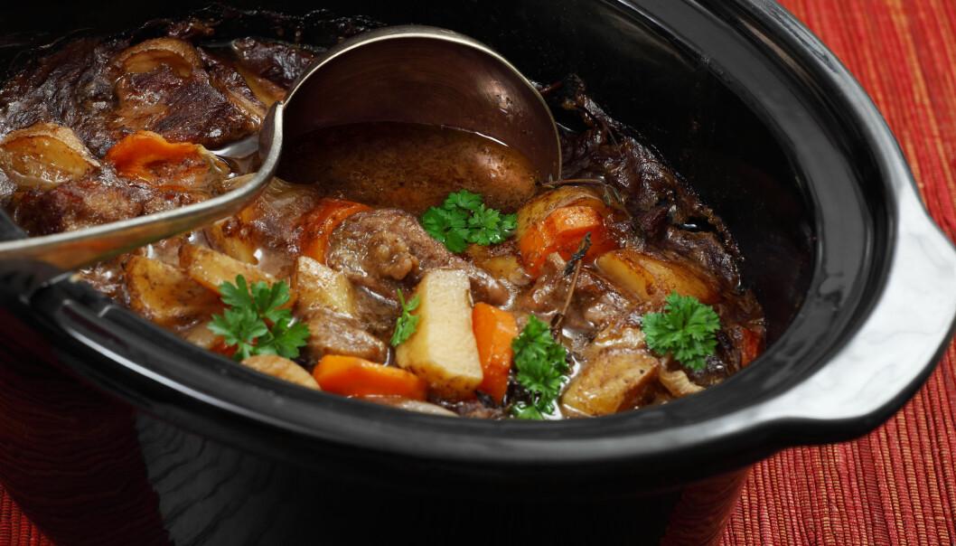 En köttgryta med morot och persilja i en slow cooker fotograferad uppifrån.