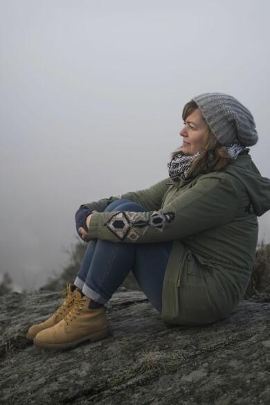 En kvinna i övre medelåldern sitter med varma kläder på en klippa och ser nöjd ut.
