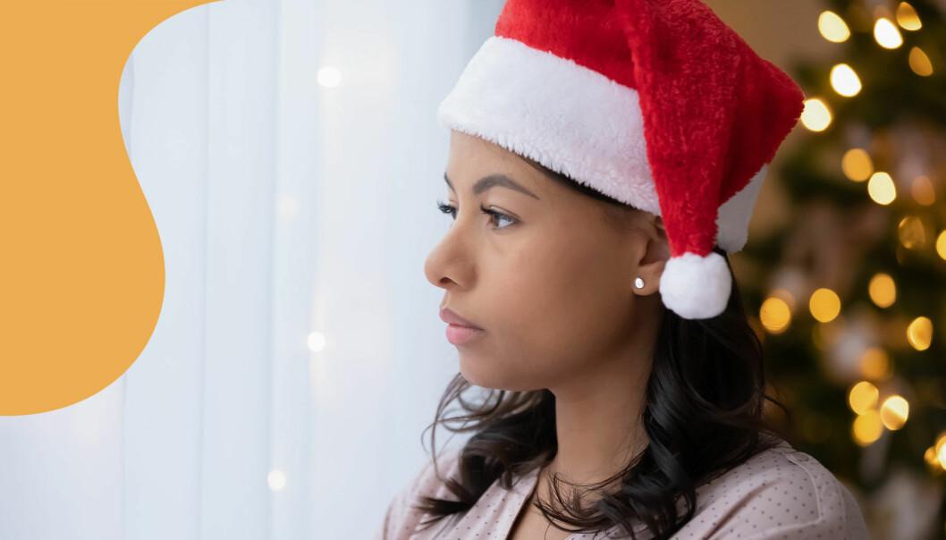 En kvinna i tomteluva tittar dystert ut genom ett fönster. I bakgrunden syns en klädd julgran.