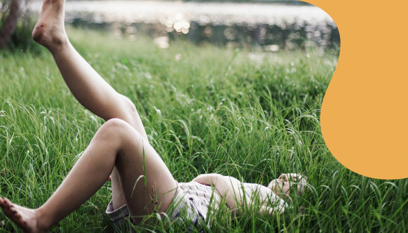 En kvinna ligger i gräset med fötterna i luften.