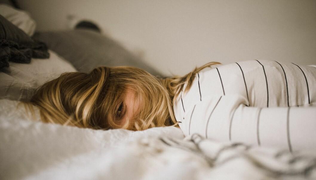 En kvinna ligger vaken på sängen och kan inte somna för snarkningar.