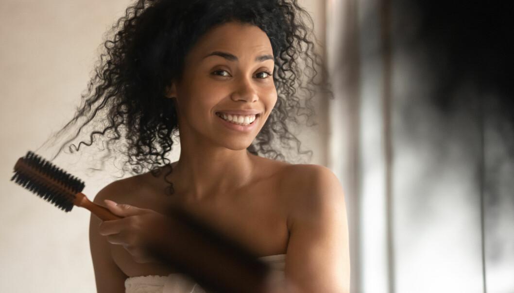 En kvinna med lockigt hår borstar med en borste som har brett mellan borsten.