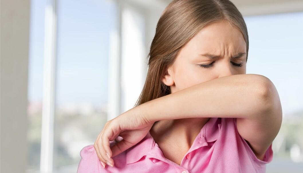 En kvinna nyser i armvecket för att inte sprida coronavirus.