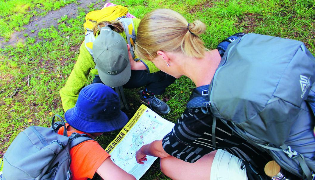 En kvinna och två barn läser en karta under en vandringstur.