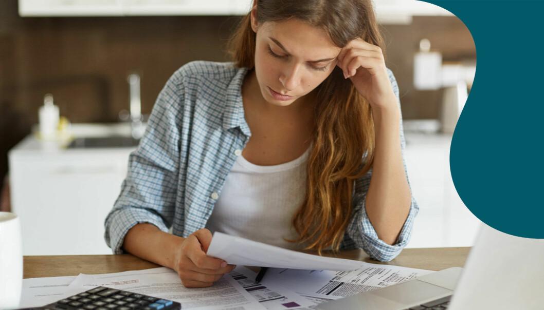 En kvinna sitter och tittar på räkningar vid köksbordet där det också finns en miniräknare och en laptop.