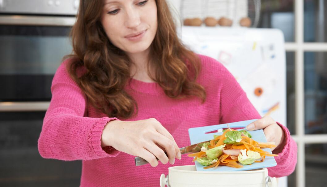 En kvinna slänger matrester i soptunnan.