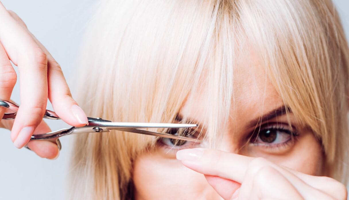 En kvinna som gör en klassisk hårmiss och försöker klippa sin egen lugg.