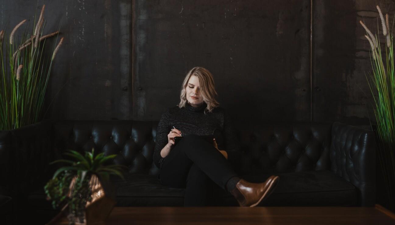 En kvinna som skulle kunna vara psykolog sitter och antecknar.