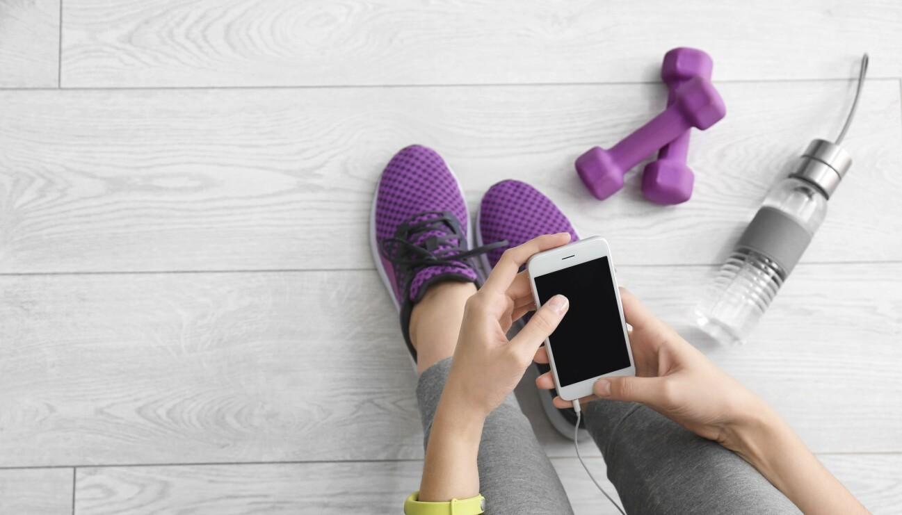 En kvinna som tränar digitalt via mobilen och ändå kan få friskvården betald av företaget.