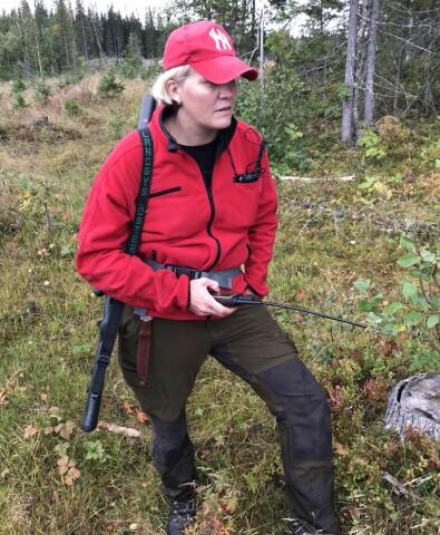 En kvinna står med gevär och walkie talkie i skogen.