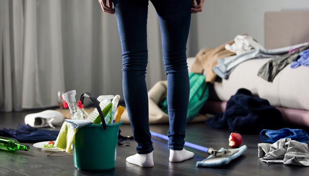 En kvinna står mitt i ett rum som är väldigt stökigt. Bredvid sig har hon en hink med städhjälpmedel.