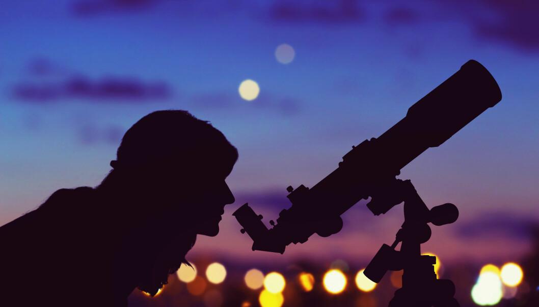 En kvinna tittar i en stjärnkikare sent på kvällen.