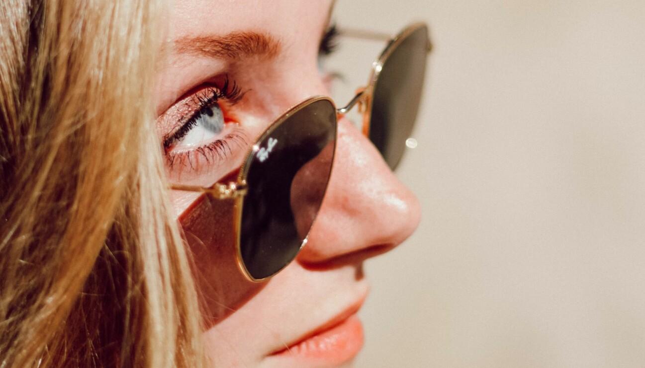 En kvinna tittar upp mot solen och skadar sina ögon.