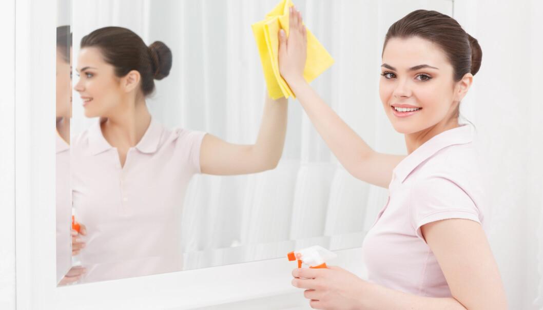 En kvinna torkar av badrumsspegeln.