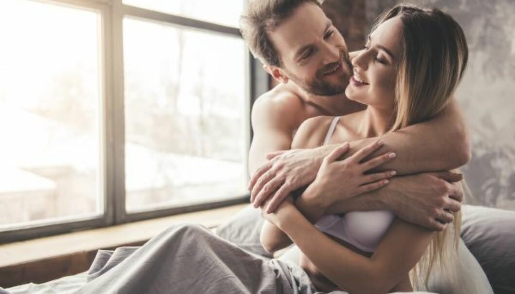 En man och en kvinna kramar om varandra, sittandes i säng.
