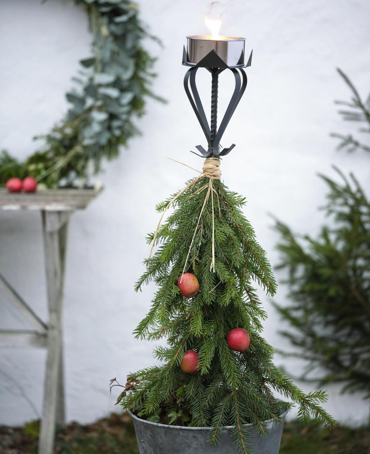 En marschallhållare dekorerad med granris och röda äpplen.