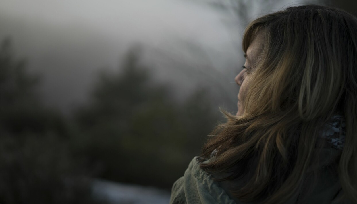 En medelålders kvinna blickar eftertänksamt ut över naturen.