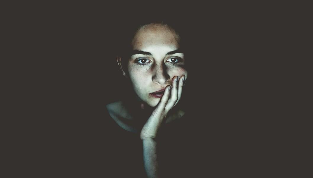 En orolig kvinna läser i ljuset från en skärm.