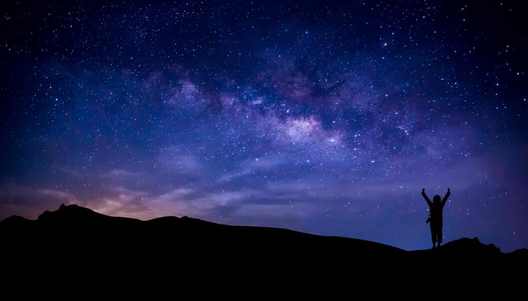 En person sträcker upp händerna mot en stjärnbeströdd natthimmel.