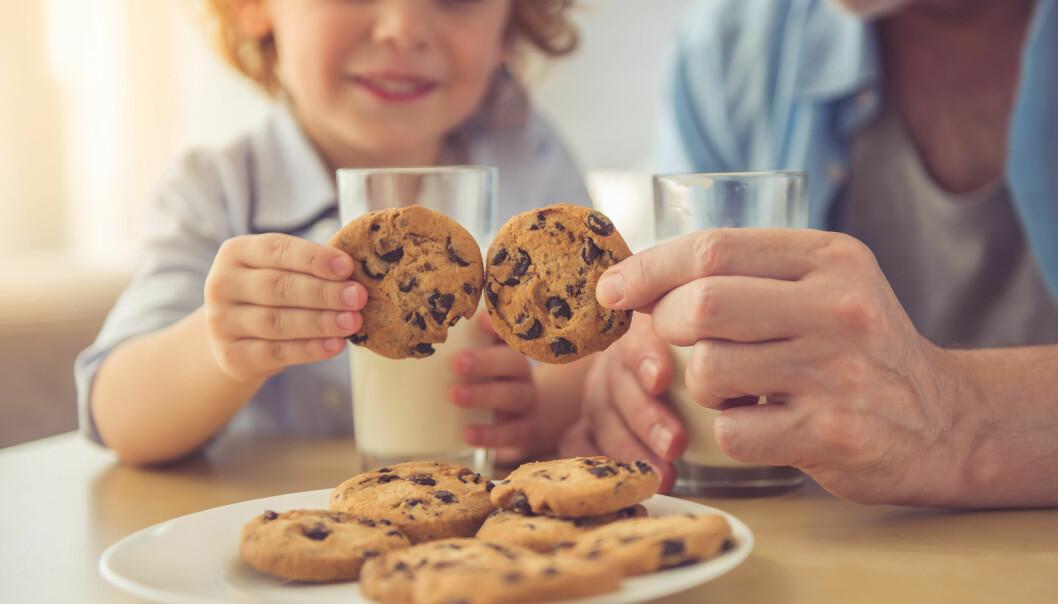 En pojke och hans pappa äter kakor.