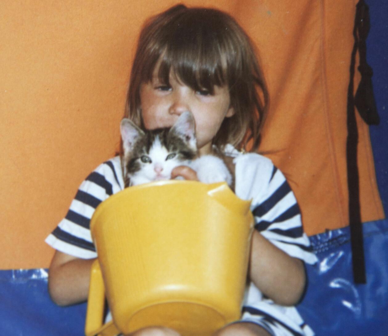 En privat bild av Sofie som litet barn, med en katt i famnen.