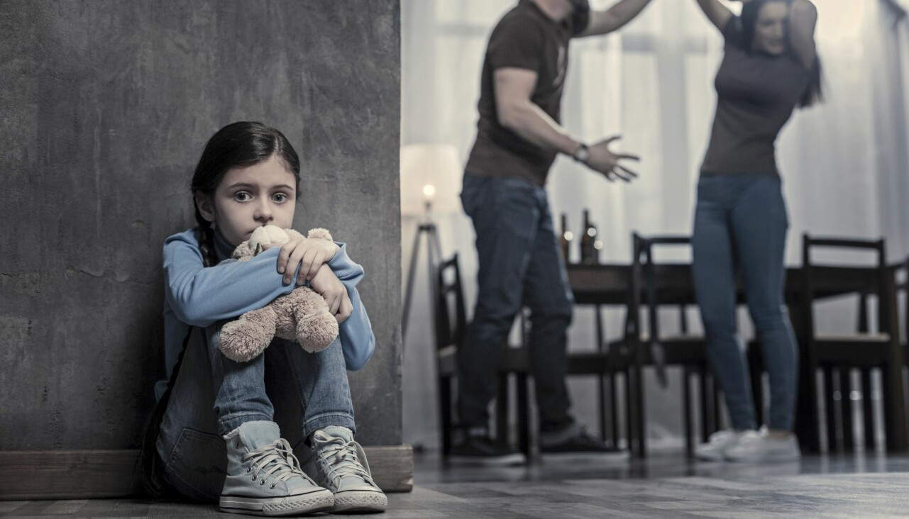 En rädd flicka gömmer sig. I bakgrunden syns hur hennes pappa misshandlar hennes mamma.