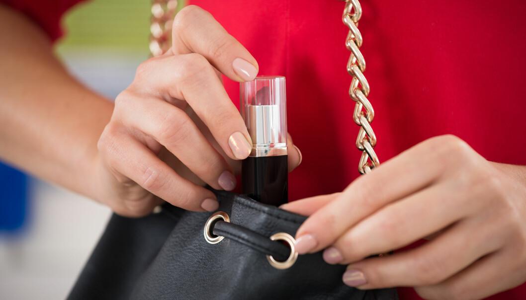 En yngre kvinnas hand smusslar ner ett läppstift i en handväska.