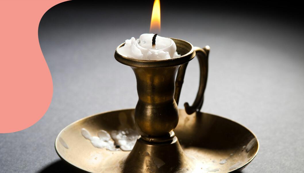 Ett brinnande ljus i en mässingsljusstake med fläckar av stearin.