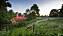 Ett ensamt får betar i en lummig, sluttande inhängnad. Det är skymning och ett rött tegelhus skymtar bakom buskagen.