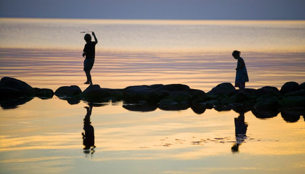 Ett par barn leker på stenar i ett grunt vatten. Det är skymning och de speglas i det stilla vattnet.
